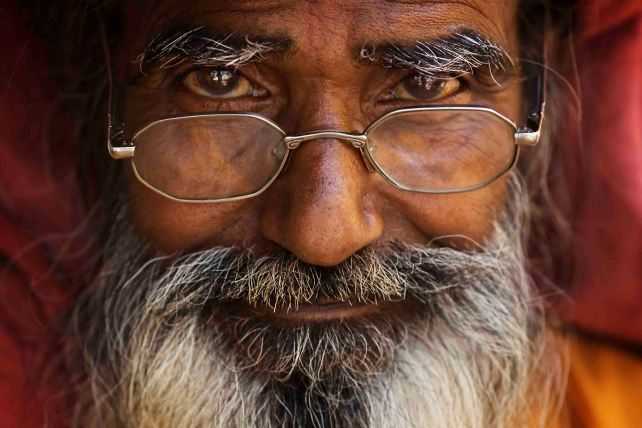 Old relaxed man, looking through glasses, Varanasi Benares India